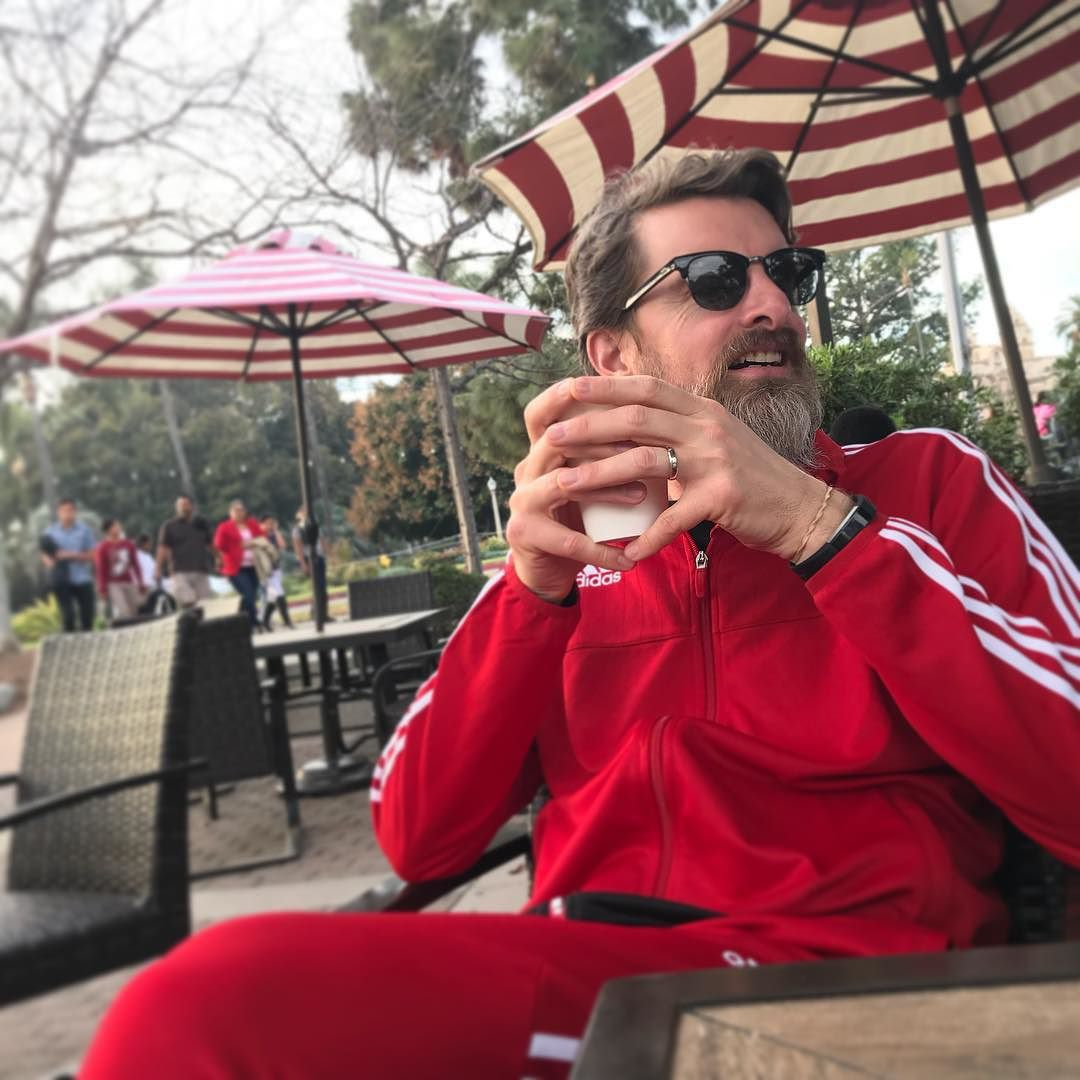 Tony Thomas in a red jogging suit holding a cup of tea with umbrellas in the background.